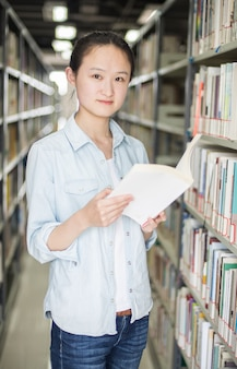 Young woman posing with a book in the library