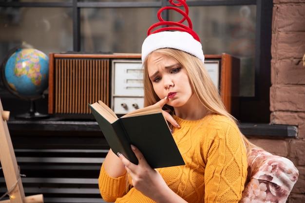 クリスマスのギフトボックスでポーズをとる若い女性。