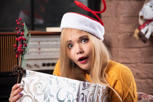 Giovane donna in posa con scatola regalo di natale.