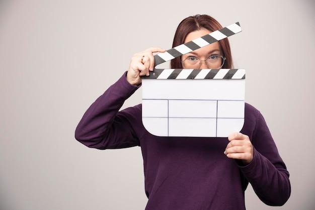 Giovane donna in posa con un nastro cinematografico su un bianco. foto di alta qualità