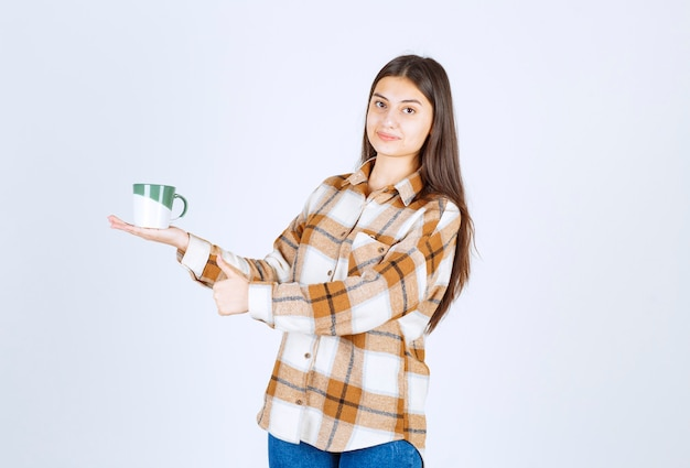 Young woman posing with cup of coffee on white wall.