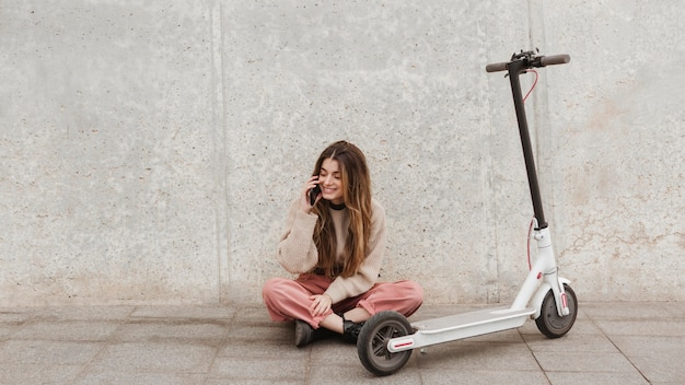 Giovane donna in posa con uno scooter elettrico