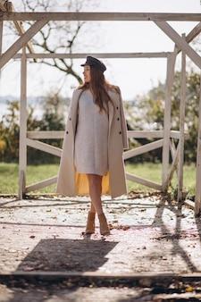 가 야외에서 패션 코트와 함께 포즈를 취하는 젊은 여자
