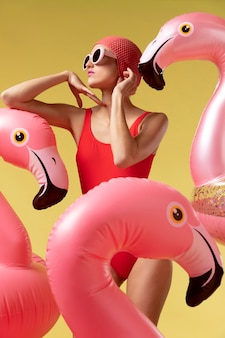 Young woman posing with flamingo swimming ring