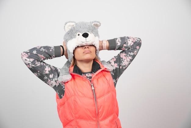 흰 벽에 재미있는 모자와 함께 포즈를 취하는 젊은 여자.