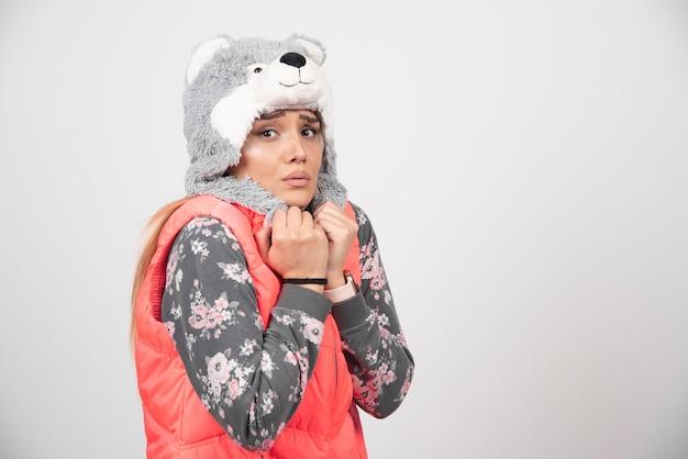 白い壁に面白い帽子をかぶってポーズをとる若い女性。