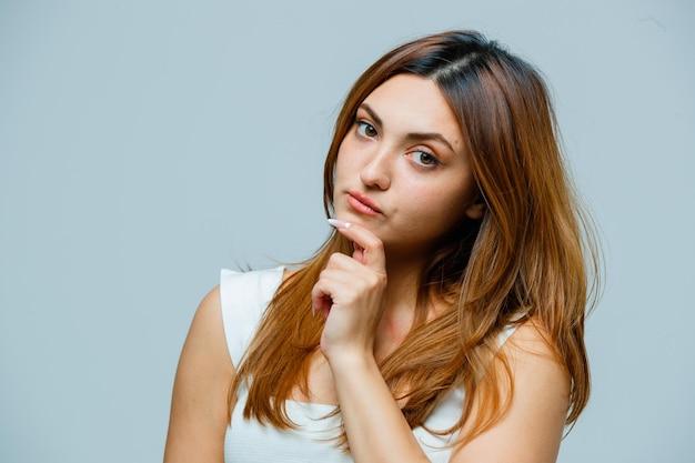 顎に手でポーズをとる若い女性