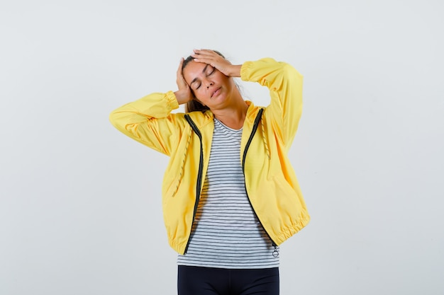 Tシャツ、ジャケット、魅力的な正面図で頭に手を当ててポーズをとる若い女性。