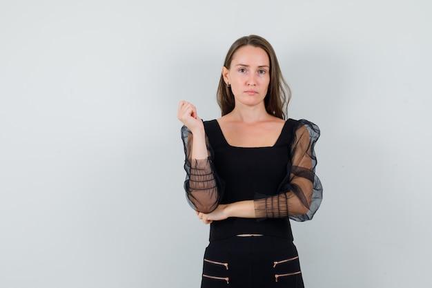 Молодая женщина позирует с ее локтем под рукой в черной блузке и выглядит привлекательно. передний план. место для текста