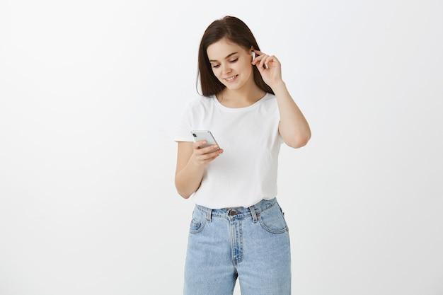 白い壁に彼女の電話とイヤフォンでポーズをとる若い女性
