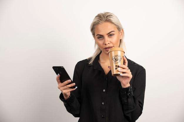 携帯電話と一杯のコーヒーでポーズをとる若い女性。高品質の写真