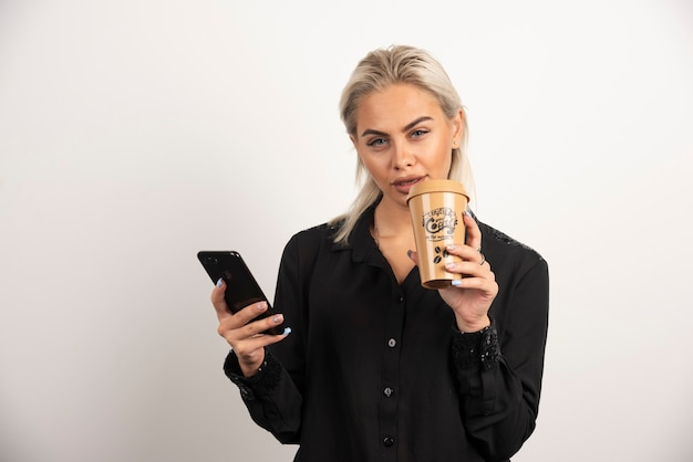 Giovane donna in posa con il telefono cellulare e la tazza di caffè. foto di alta qualità