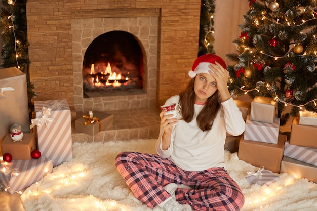 Young woman posing with mug of coffee or tea on background of fireplace, fir tree and gift boxes