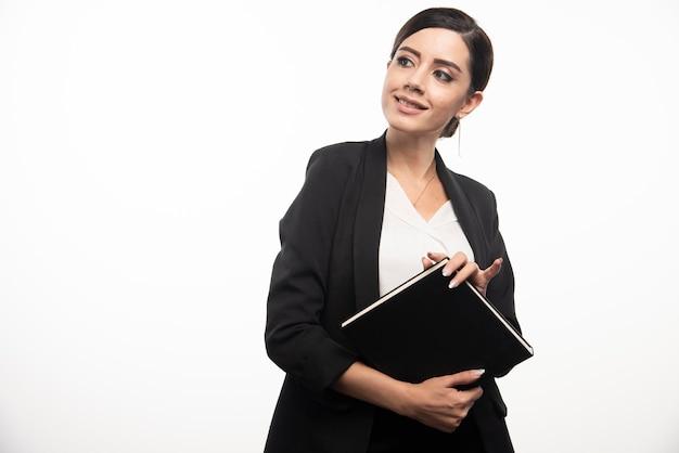 Молодая женщина позирует с ноутбуком на белом фоне. фото высокого качества
