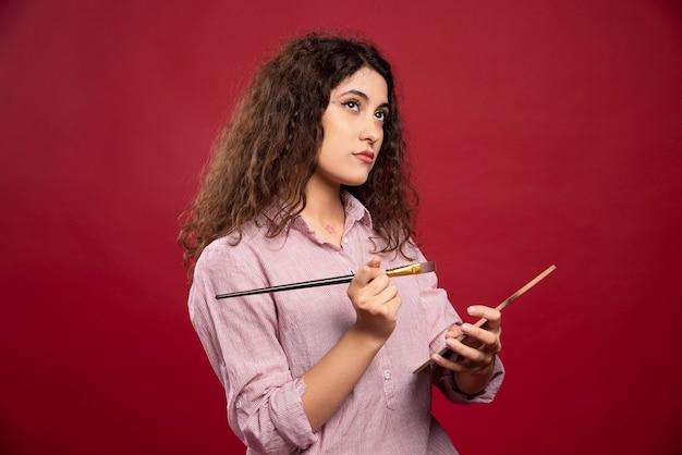Giovane donna in posa con pennello e tavolozza di vernice.