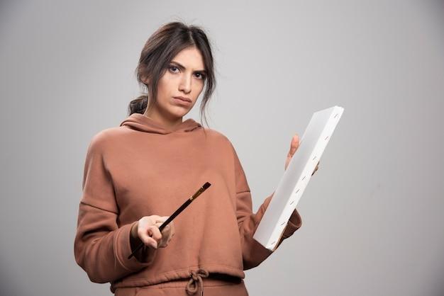 Giovane donna in posa con pennelli e tela