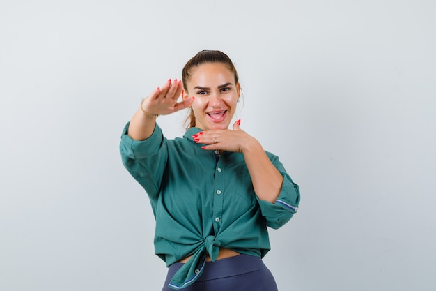 Young woman posing with palm outward to stop in green shirt and looking happy. front view.