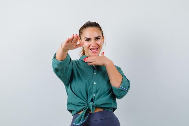 緑のシャツを着て立ち止まるために手のひらを外側に向けてポーズをとって幸せそうに見える若い女性。正面図。