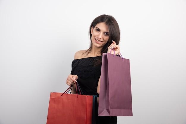 젊은 여자는 쇼핑백과 함께 포즈.