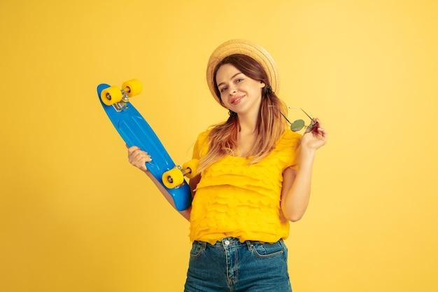 스케이트 보드와 함께 포즈를 취하는 젊은 여자