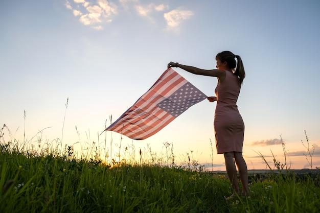 Молодая женщина позирует с национальным флагом сша на открытом воздухе на закате. положительная женщина празднует день независимости соединенных штатов.