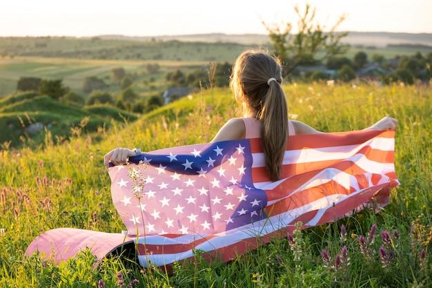 Молодая женщина позирует с национальным флагом сша на открытом воздухе на закате. позитивная девушка празднует день независимости соединенных штатов.