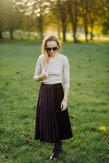 Young woman posing over yellow leaves in the autumn park. outdoor