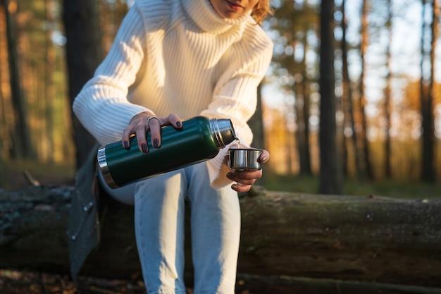 컵에 보온병에서 뜨거운 차를 붓는 젊은 여성은 혼자 가을 숲을 산책하는 하이킹에서 휴식을 취합니다