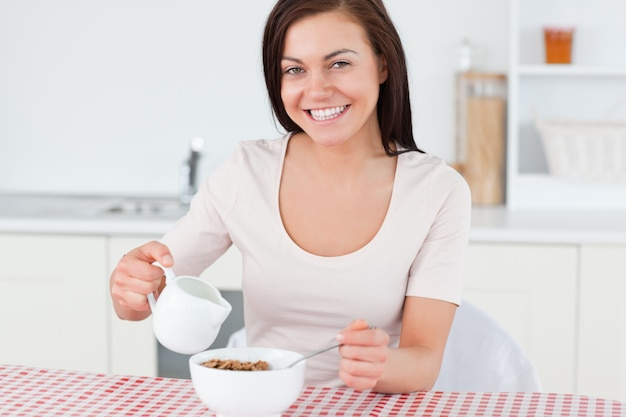 Young woman pouring milk in her cereal