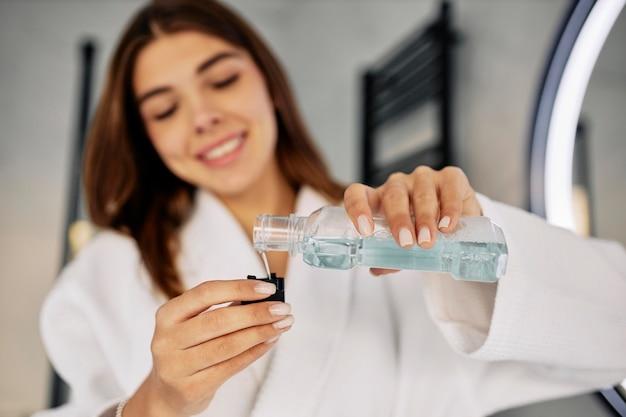 うがい薬を注ぐ若い女性
