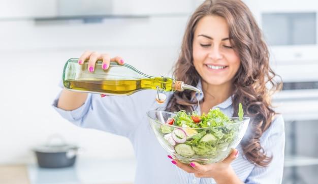 Молодая женщина наливает оливковое масло в салат. концепция питания здорового образа жизни.