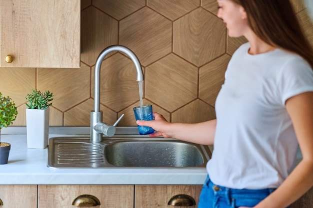 Young woman pouring running purified filtered tap water in glass at kitchen for healthy drinking