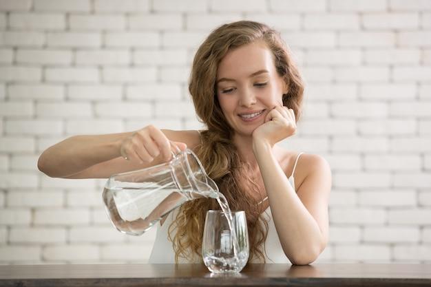 部屋のガラスに水差しから水を注ぐ若い女性