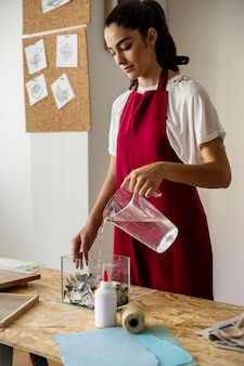 Young woman pouring water in glass container filled with torn papers