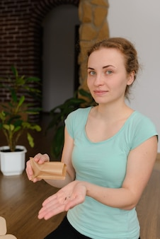 Young woman pours arugula seeds for planting in a microgreen soil substrate.  home gardening