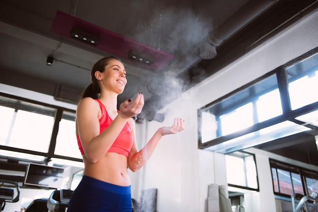 Young woman powder hands before exercise in the gym