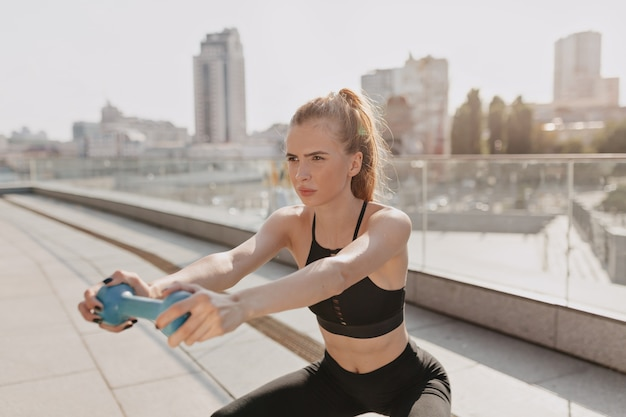 若い女性は、日光の下でハンドダンベルを使って屋外でストレッチを練習します。高品質の写真