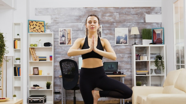 Young woman practice wellness doing yoga pose in living room.
