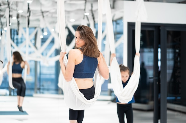 Young woman practices aerial anti-gravity yoga