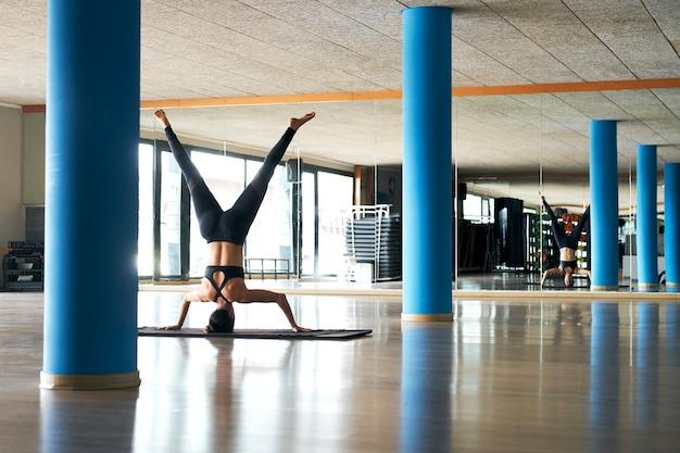 若い女性はジムでのヨガセッションでバランスアーサナを練習します。 salambasirsasana-サポートされている倒立
