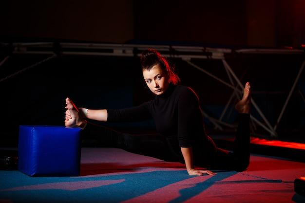 若い女性はひも座りを練習します。体育館で体操をしているアスレチックガール。アクティブなライフスタイル