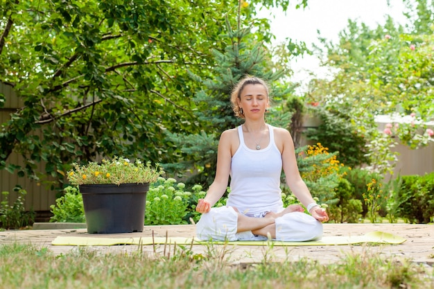 Young woman practices yoga in the garden