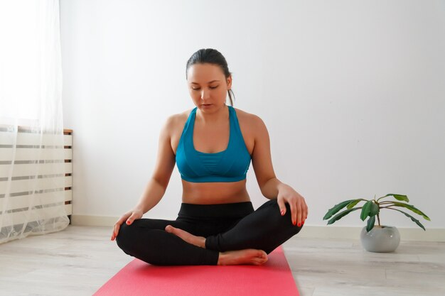 Young woman practices yoga at home, meditating and sitting on a mat. against the white wall.