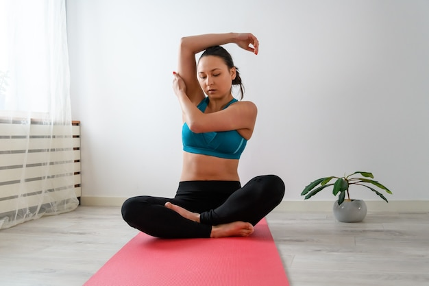 Young woman practices yoga at home sitting on a mat.