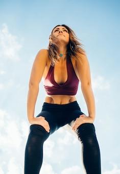 젊은 여자는 외부 요가 관행. 평온한 평화로운 소녀는 무릎 위의 다리에 손을 대고 서 있습니다. 그녀는 진공과 나 울리를 연습합니다. 아래에서 보는 풍경. 하늘과 구름