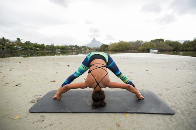 Young woman practices yoga on the shore of the indian ocean