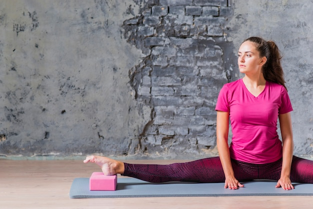 Young woman practicing advanced yoga using pink block against grey wall
