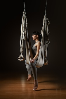 Young woman practicing aerial yoga hammock indoors