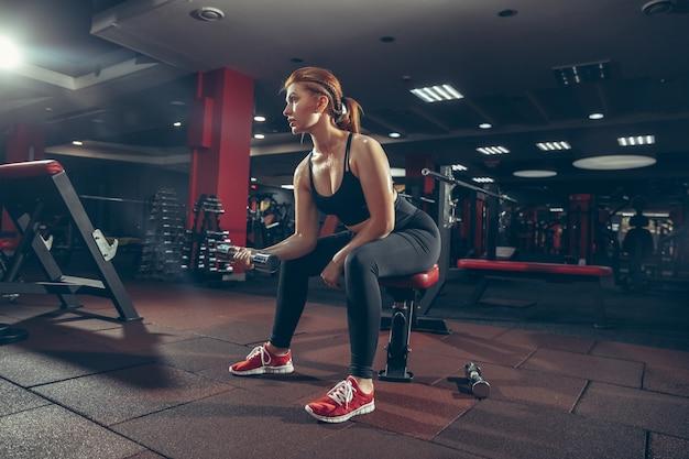 機器を備えたジムで練習している若い女性。運動、トレーニングボディを行う運動女性モデル