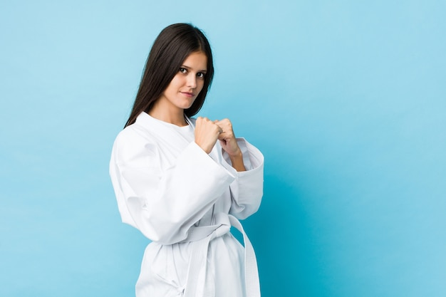 Young woman practicing karate isolated on a blue wall